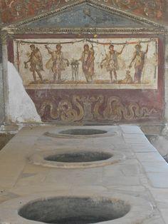 Pompeii | Flickr: partage de photos! Thermopolium avec le comptoir et au fond le lararium et la fresque au génie / serpent.