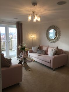 Pink sofa living room feature round mirror pastel colours