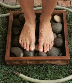 Designate a grassy spot a step away from your porch or patio as the place for washing sandy feet before re-entering the house. Make a weatherproof frame with four three-inch-tall boards. The box shown is 16 inches square.  Fill it will several layers of smooth, flat stones - river stones look particularly handsome and are easy on the soles. Sand rinses away into the stones and grass below, leaving bare feet clean.  Martha Stewart Living, July 2001