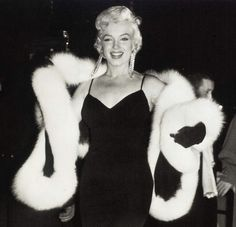 A black silk jersey stole trimmed with white fox fur sold for $49,946, along with this photo of Marilyn wearing the stole, at a December 200...