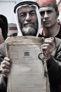 Palestinian man holds the key and deed to a home that no longer exists.