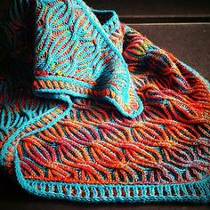 'Fire in the Sky' is a triangular shawl, worked bottom-up in two-color brioche, combined with cables. The body is surrounded by an I-cord, a small border, worked in the round, and a second I-cord.