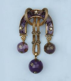 AN ANTIQUE AMETHYST, PEARL AND DIAMOND BROOCH   Designed as a horse-shoe shaped body set with calibrated amethysts, partly interspersed with pearl and diamond set stars, the centre with rope tied gold thread strung with two diamond set crown slides, supporting three amethyst spheres encrusted with rose-cut diamond set four-leaf clover appliques, circa 1870