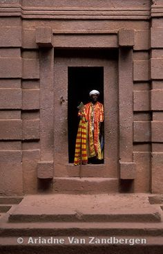 Priest at the entrance of Bet Emanuel rock-hewn church. 12m high monolith below ground level, Lalibela, Ethiopia