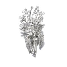 Diamond brooch Of floral spray design, the flowers set en tremblant with pear-shaped and brilliant-cut diamonds, to the baguette diamond stems and pavé-set diamond leaves, French assay and maker's marks.