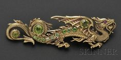 Art Nouveau 14kt Gold, Peridot, and Demantoid Garnet Dragon Brooch, Riker Bros., the writhing dragon with circular-cut peridot and demantoid garnets, ruby melee eye, lg. 3 1/8 in., maker's mark, in a period fabric box.