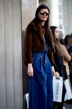 A short chocolate brown faux fur jacket over denim blue jeans with a accentuated waist, bow tie belt, a narrow sewn waist and fabric gathered low, at the hips and from there flows out to a wide legged pair of trousers.
