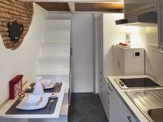 Italian micro apartment, just 75 square feet. Fold down dining table uses stairs for seating.
