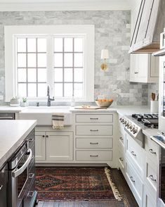 white kitchen + marble tile + rug