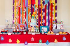 rainbow raindrops colorful play date birthday party baby shower dessert table with drops banner colorful streamers and paper link chain backdrop