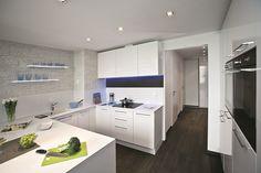 Priestor kuchyne s bielou kuchynskou linkou zjemňuje drobný raster obkladu s imitáciou bieleho prírodného kameňa a tiež jednotný drevený prvok na zástene kuchynskej linky a podlahe.