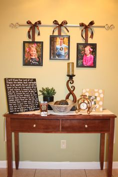 Curtain Rod Picture Display -- Made this with much help from my fantastic mom! Used 5 pics instead of 3, black rod, and satin white ribbon.. It's hanging in our dining room.. Love it!