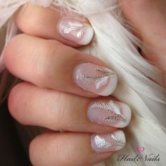 Beautiful white themed feather nail art. You can use a readymade synthetic feather for this design. Begin with a classic French tip in white polish on your nails. Then add the synthetic feather on top, make sure it is trimmed well before applying the final coat.