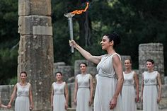 The flame is lit An actress dressed as a high priestess holds up a torch with the Olympic flame. The flame will travel to London after a week-long relay throughout Greece.