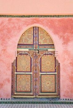 Dreaming of Marrakesh, Morocco after seeing this gorgeous arched doorway with intricately carved and decorated patterned front door, framed by pretty pink plaster walls.