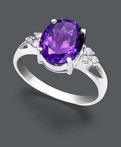 Perfection in purple. Ring features a classic design set in 14k white gold. Center stone features a brilliant oval-cut amethyst (2-1/3 ct. t.w.) and a triangle of three round-cut diamond accents (1/10