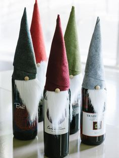 "DIY Wine Elf - To dress up a bottle of wine as a holiday hostess gift, cut felt into an 8x10 rectangle and faux fur into a triangle roughly 2 inches wide by 4 inches long. Wrap felt rectangle into a cone shape, securing the edges with fabric glue as you wrap. Glue the faux fur ""beard"" to the inside of the felt ""hat"" and finish with a small pom-pom ""nose."""
