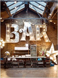 Big light-up fairground light in industrial warehouse wedding setting.