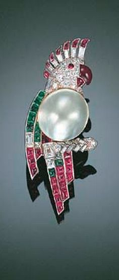"AN ART DECO MULTI-GEM AND DIAMOND ""PARROT"" BROOCH, BY CARTIER With blister pearl body and pavé-set diamond head to the diamond and ruby crest, eye and beak, the plumage channel-set with French-cut diamonds, buff-top emeralds and rubies, perched on a diamond-set branch, mounted in platinum, 1933, 5.0 cm high Signed Cartier London, no. 1405"
