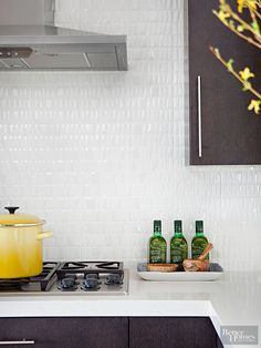 Glossy triangular tiles boasting irregular angles are strategically spaced in a sea of white grout to create a pillowed effect. The glistening backsplash introduces understated but notable texture that layers in detail without detracting from the kitchen's contemporary character./