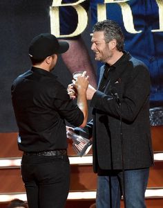 """Luke Bryan Photos Photos - Blake Shelton (R) presents honoree Luke Bryan with an award onstage during the 2015 """"CMT Artists of the Year"""" at Schermerhorn Symphony Center on December 2, 2015 in Nashville, Tennessee. - 2015 'CMT Artists of the Year'"""