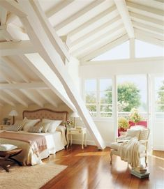 Contemporary cottage attic bedroom with sloped white beamed ceiling, honey wood floors and balcony.