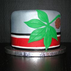 O-H-I-O - Birthday cake for my co-worker's hubby. Red velvet cake (what else?). Chefmaster Silver Spray for the silver finish. And by the way... those skinny stripes were a pain in the you-know-what! If anyone has suggestions for how to pick them up without stretching, I'd love to hear it!!!