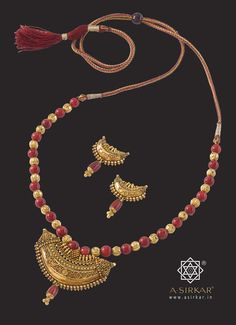 Dholavira Necklace :  Fusing ancient techniques of beaten gold and thick wire decorations with ultra-fine reji-work, this chunky pendant is beautifully complemented by the red beads and dholak pola drop. Yet, that's not to say that it would not look equally attractive with pearls, lapiz-lazuli or black beads. Perfect for a Puja evening -- perfect anytime. With matched earrings, all in hallmarked 22K yellow gold.