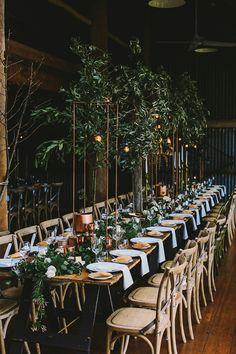 Beautiful long farm table setting with loads of greenery and details! indoor garden reception - photo by Lara Hotz Photography http://ruffledblog.com/botanical-australian-barn-wedding