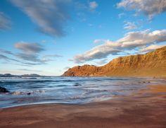 Los Riscos de Famara. Los Riscos de Famara La playa de los Riscos de Famara está situada al norte de la isla de Lanzarote, entre Teguise y Haría. De arena blanca, su principal atractivo (además de su soledad habitual) son sus paredes verticales de roca y la posibilidad de practicar surf y kitesurf.