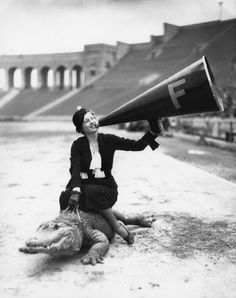 A woman riding an alligator in the Los Angeles Memorial Coliseum. The alligator is evidently the team mascot, c 1930s (via Los Angeles Public Library)