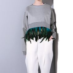 Stylish sweatshirt with removable chic feather fringes. Sweatshirt features crop front and longer back. One size fits all. Made of cotton and feathers. Note: Ships within 7 days.