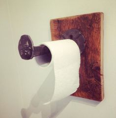 Toilet paper holder made from old washer welded on a railroad spike on reclaimed wood.