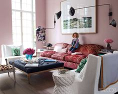 D'Ornano's daughter Inès in the back drawing room, which has walls upholstered in pink linen; the sofa is by George Smith, and lamps by Serge Mouille flank a photograph of Beirut by Elger Esser.