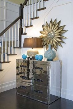 Mirrored chest with gold bronze sunburst mirror. Love the blue turquoise accents in this entrance foyer! White paneling (wall panels) in entrance foyer! Mirrored Furniture, Mirrored Dresser, Chest Dresser, Coastal Living Rooms, Cozy Living, Sunburst Mirror, Coastal Decor, Coastal Bedding, Modern Coastal