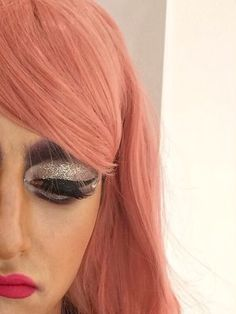 Drag makeup silver and purple look with a pink styled wig.