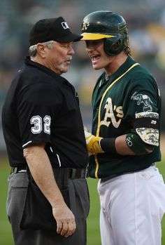 Josh Donaldson #20 of the Oakland Athletics argues with home plate umpire Dana DeMuth #32 after Donaldson was called out on strikes