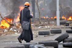 An Orthodox priest walks under fire during clashes between anti-government protesters and riot police. (Sergei Supinsky/AFP/Getty Images)