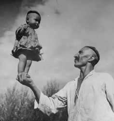A #Uyghur man holding a baby on the palm of his hand. Photograph by William #Vandivert  #Sufism #Islam #China #Mysticism #Spirituality