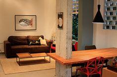 Sala de estar e jantar integradas. Mesa de madeira Ipê engastada em pilar de concreto aparente. Pilar descascado. Luminária pendente. Quadros decorativos. Mesa de centro Fernando Jaeger. Parede com pintura verde.