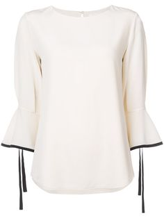 Ivory and black top featuring a silk ruffle sleeve and self-tie detail.