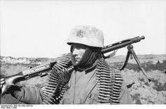 German paratrooper in the eastern front. 1943. He's carryng a MG-42 machine gun.