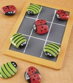 Home Made Tick Tack Toe Painted Stones      Would be cute with flat glass marbles with their pic on bottom