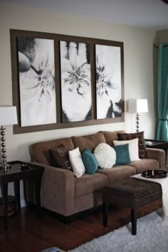 teal accents on a chocolate brown couch and black and white photographs.
