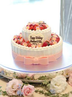 おふたりのウェディングケーキは、二段タイプでピンクのリボンとお花のモチーフがアクセント♡披露宴は可愛らしくしたいという結婚式のテーマにもピッタリですね。