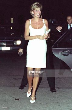 Princess Diana Attending A Concert In Italy In Aid Of Bosnian Children. The Princess Is Wearing A Short White Dress And White Shoes.