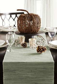 Create a simple fall tablescape to carry you through the season. A grapevine pumpkin and other natural elements complement mercury glass votives for an elegant look.