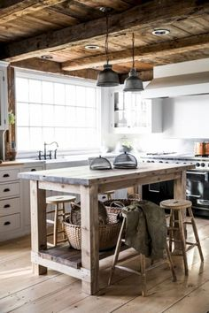 40+ Best Farmhouse Kitchen Island Decor Ideas On a Budget Rustic Farmhouse kitchen, wood island with zinc counter, wood beamed ceiling and wood floors, white cabinets, pendant lights, goose neck faucet, neutral color palette, copper pot, recessed lighting, european stove and natual lighting, wooden bar stools