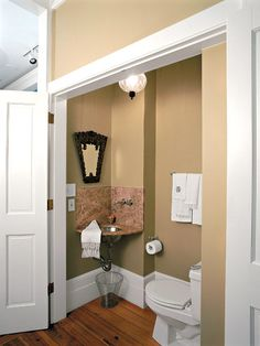 Small powder room under a flight of stairs.