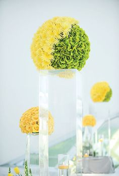 Two-tone floral orb atop a tall vase pedastal. Green roses are silk/artificial but yellow chrysanthemums are fresh flowers.